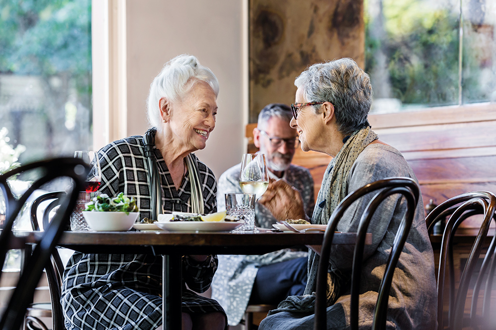 Two senior women dining at La Luna café, Carlton